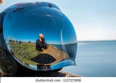 A man in the reflection of a motorcycle helmet sits on the seashore