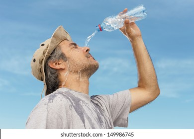 Man refreshing himself with water, outdoor shot.