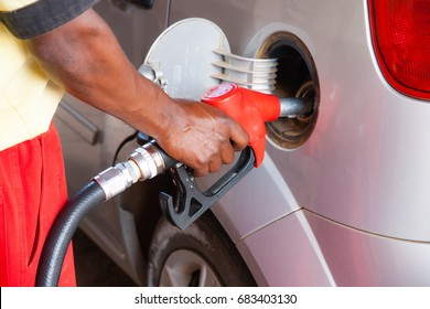 Man refueling a car at the petrol station. Concept photo for use of fossil fuels (gasoline, diesel) in combustion engines, air pollution and environmental and occupational health.