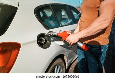 man refuels a car at a gas station
