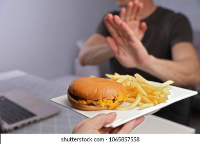 Man refuses to eat junk food . Healthy eating and active lifestyle concept, high cholesterol and high blood pressure prevention