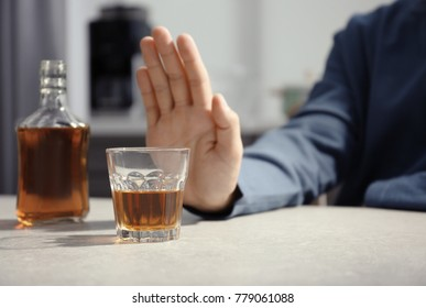 Man rejecting glass of alcohol indoors