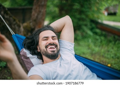A man rejoices and laughs while lying in a hammock. Close-up. A young guy lies in a hammock, rejoices in the fresh air in the summer in the green of trees in the country
