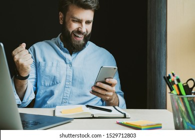 Man rejoices in victory while looking at screen of smartphone. Creative worker at desk with laptop and notebook. Young professional using phone to surf internet. Male specialist getting high-paid job.