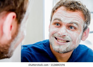 A man with a rejuvenating mask on his face looks in the mirror and smiles