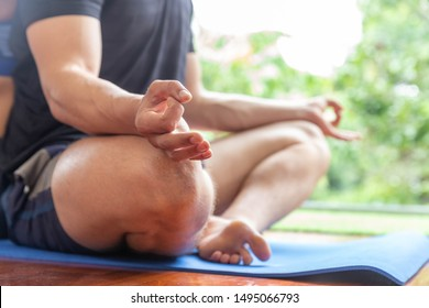 A man relax exercise yoga at home, close up at his hand