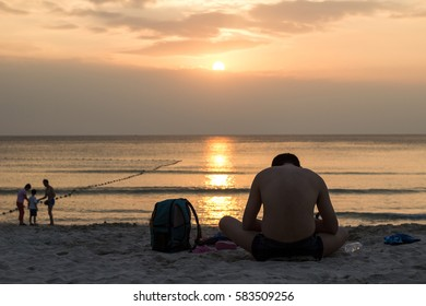 Man relax on the beach with sunset background