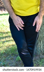 man in relaxed athletic clothes yellow black holding his itchy crotch leaning against a tree outdoors background