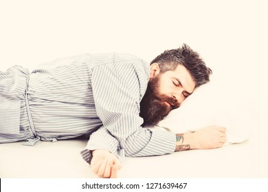 Man with relaxed face lies on pillow. Hipster with beard fall asleep. Fast asleep concept. Man with beard and mustache in deep sleep, white background. Hipster drowsy, wants to sleep, copy space.