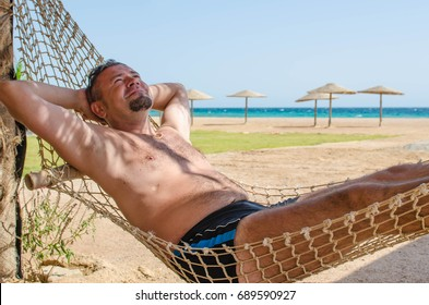 Man relaxed and lies on a hammock on the beach