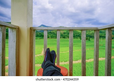Man relaxed on chair looking on rice fields in Thailand