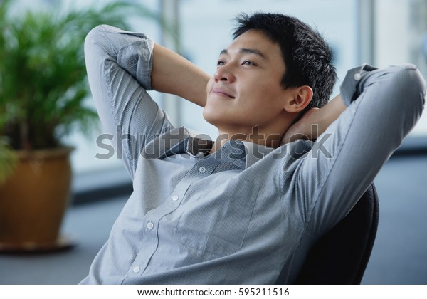 A man relaxes at his desk