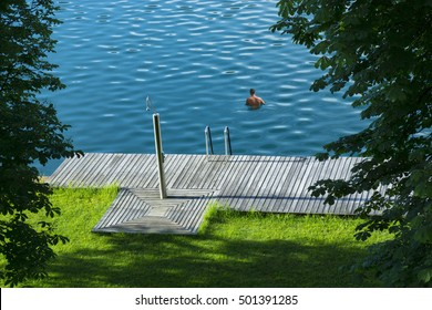 Man relaxes in an idyllic outdoor lakeside swimming pool