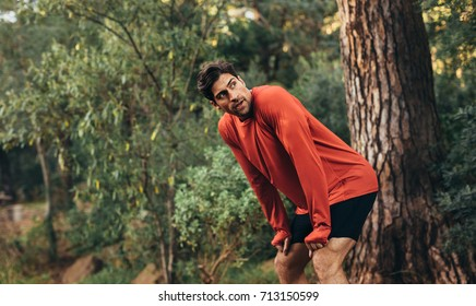 Man relaxing after intense workout. Athlete taking rest with hands resting on knees after a run.