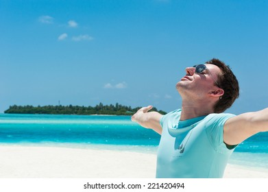 Man relaxing at beach enjoying summer freedom with open arms. Man on summer travel holidays vacation