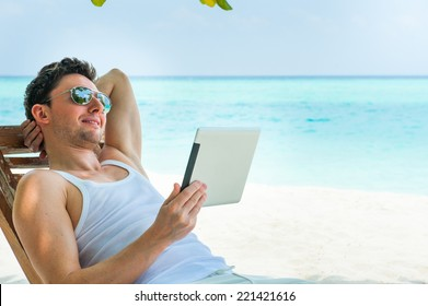 Man relaxing at the beach with tablet, laptop. Maldives island, ocean view