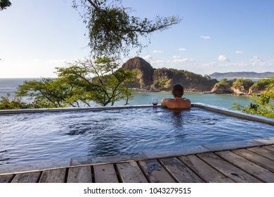 man relaxing in a  calm pool with an amazing view of the pacific ocean