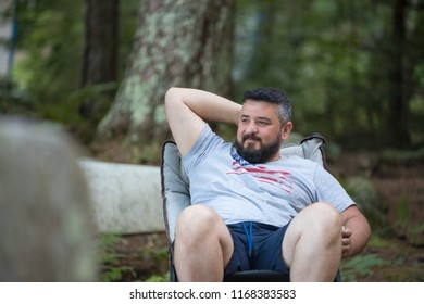A man is relaxing at a camp site