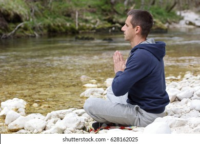 Man relaxing, doing yoga after jogging, workout in beautiful nature landscape. Sport and healthy life style concept