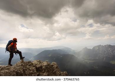 Man relaxing in Dolomites with via ferrata equipment / Dolomiti mountains, Catinaccio / Rosengarten, Torri del Vajolet / Vajolet, Beautiful landscape