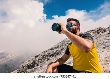 Man relaxing and drinking water after trekking with Dolomites mountains in the background, Italy.