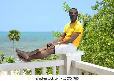 Man relaxing with feet up sitting on a post