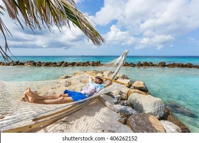 Man relaxing in a hammock at Flamingo beach. Aruba island