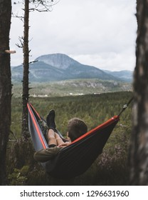 man relaxing in hammock in the forrest mountain landscape view norwegian norway sigdal summer trip holyday vacation sleeping outdoor natue