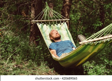 Man relaxing in hammock. Young caucasian man with beard swinging and resting in a hammock in a pleasant laziness of a summer outdoor weekend. Outdoor, adventures and nature vacation.