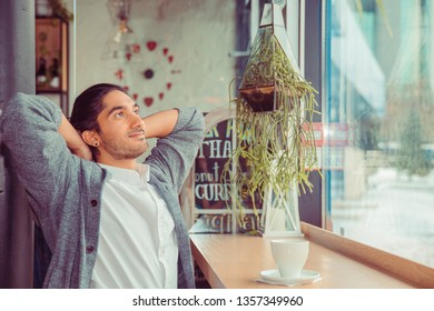 Man relaxing hands behind head breathing free, enjoying life happy, dreaming about future. Closeup portrait of handsome guy wearing white shirt, gray blouse sitting near window at a table near window