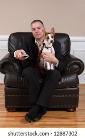 A man relaxing with his dog and his remote control after a long day at work.