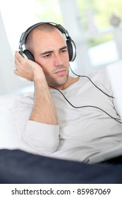 Man relaxing at home with headphones on
