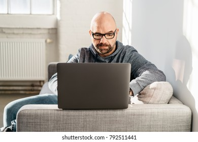 Man relaxing at home on a comfortable couch working on a laptop balanced on the arm of the furniture
