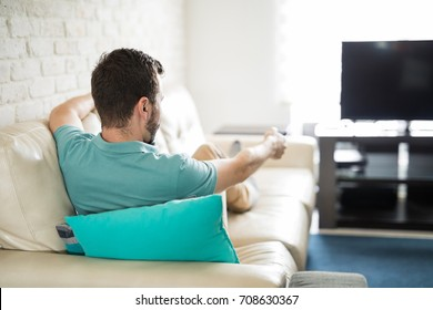 Man relaxing at home sitting in his cozy sofa holding a remote control in his hand and deciding what to watch on tv