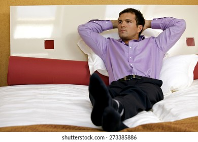 Man relaxing in hotel room with hands behind head