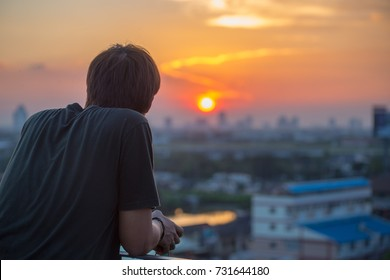 Man relaxing and looking at view of city sunset, pollution smog with orange sky background in Bangkok, Thailand.