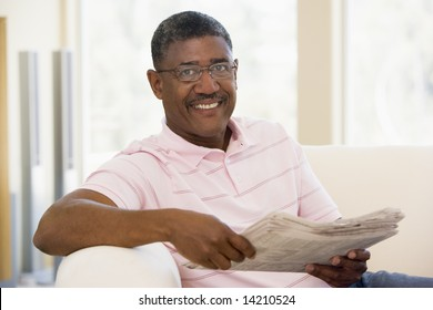Man relaxing with a newspaper smiling