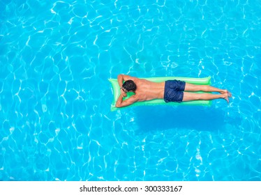 man relaxing on the air bed in the swimming pool.  vacation and free time