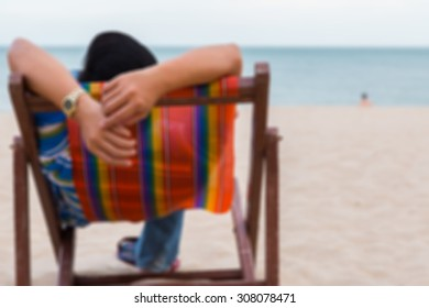 man relaxing on beach chair on the sand with sky background