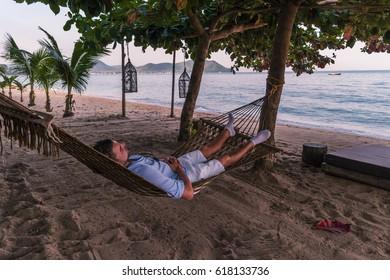 Man relaxing on the beach with a hammock under the tree,Bangsaray Pattaya Thailand february 2017 man in hammock relaxing chilling on the beach