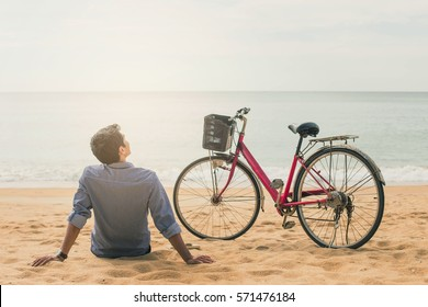 Man relaxing on the beach with red bicycle .Holiday on the beach. Relaxed young man sitting on the sand with  red bicycle enjoying sunset. Vintage style.