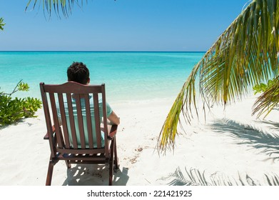 Man relaxing on chair, near palm trees, Maldives islands