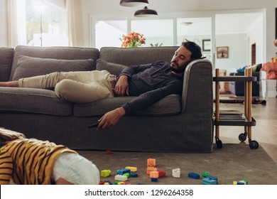 Man relaxing on couch with his kid playing on floor. Kid playing on floor with building blocks while father is sleeping on couch.