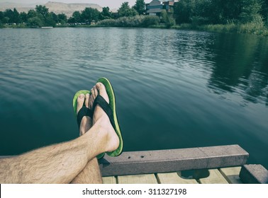 man relaxing on a dock out on a pond with a view of the office buildings around the calm pond with a toned and faded filter