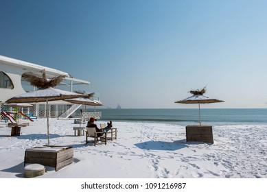 A man relaxing on a snowy beach