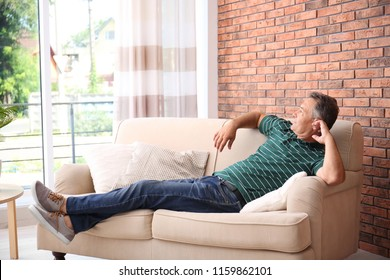 Man relaxing on sofa with comfortable pillows at home