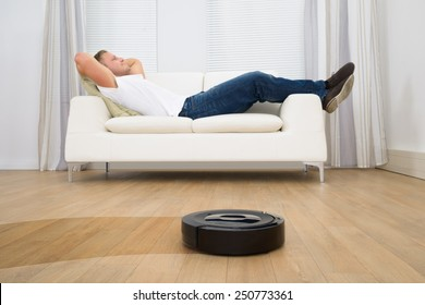 Man Relaxing On Sofa With Robotic Vacuum Cleaner On Hardwood Floor