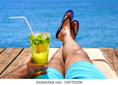 Man relaxing on sunbed and sunbathing with a cold mojito drink on the wooden beach pier. Summer vacation concept image.