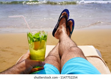 Man relaxing on a sunbed and sunbathing with a cold mojito drink on the beach sand. Summer vacation concept image.