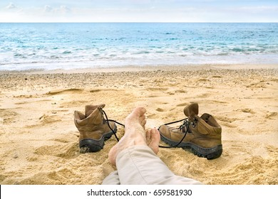 Man relaxing on a tropical beach on the sand with his leather hiking boots set to the side and a view of the calm ocean in a first person perspective.